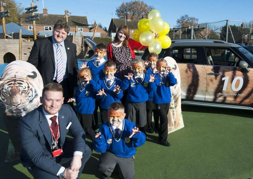 Pictured in front right Student Joshua Barnes competition winning design ona BMW Mini of Howard Junior Schoo King's Lynnl with on left Mike Jones of Listers King's Lynn with Greg Hill (Headteacher) Georgie Peats (Class Teacher) with students of Howard Juinor School.