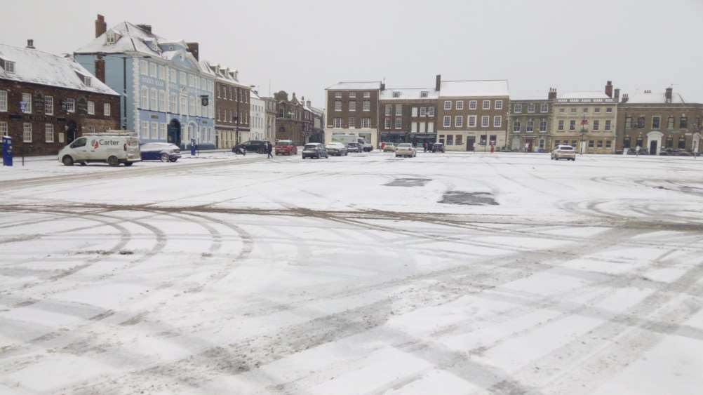 The snowy scene in a near-deserted Tuesday Market Place in Lynn this morning