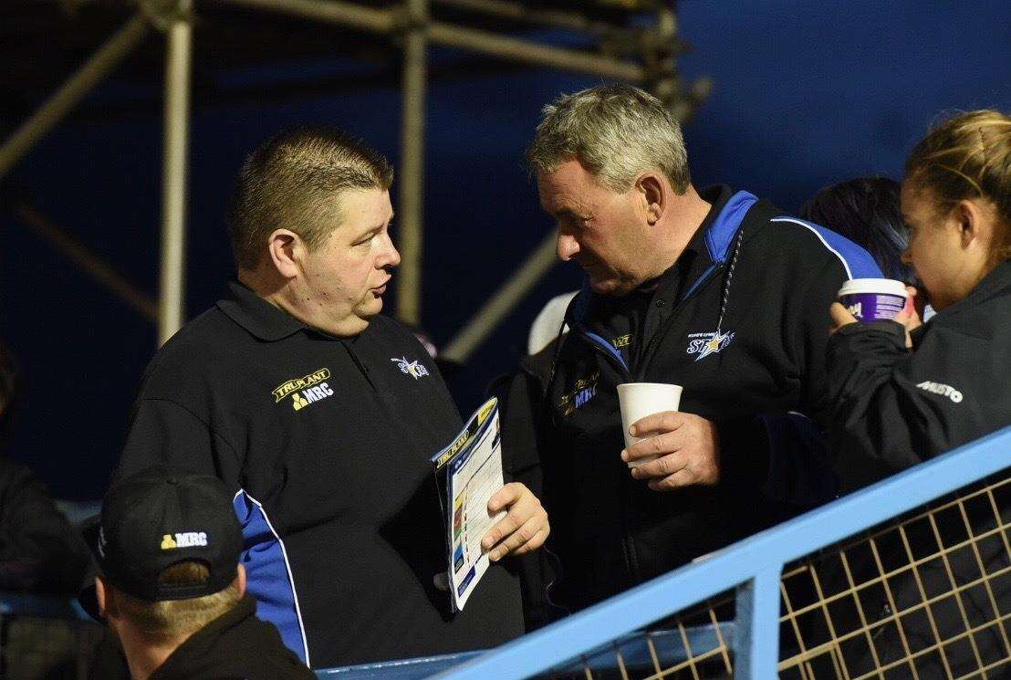 King's Lynn Stars owner and co-promoter Buster Chapman, far right, in conversation with team boss Dale Allit at the Adrian Flux Arena.