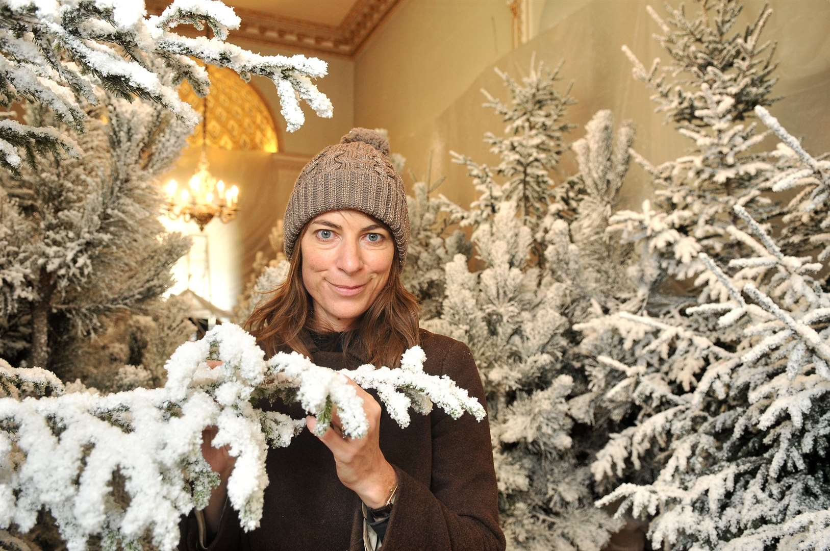 Snow covers the trees at Holkham Hall ready for Christmas. Lady Coke in the almost finished Statue Gallery
