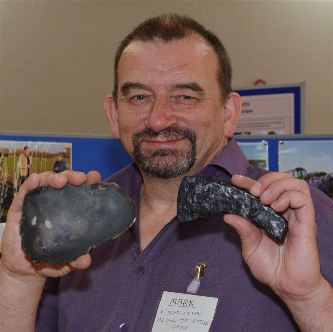 Metal detectorist, Mark Nicholson, vice-chairman of the West Norfolk Search and Recovery Group displays two of the club's finds - a Stone-Age flint axe head and a Roman iron axe