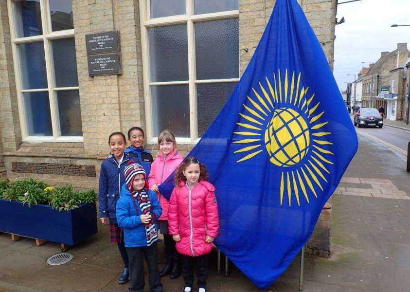 Children of various Downham Market schools with the Commonwealth Flag. Photo: SUBMITTED.
