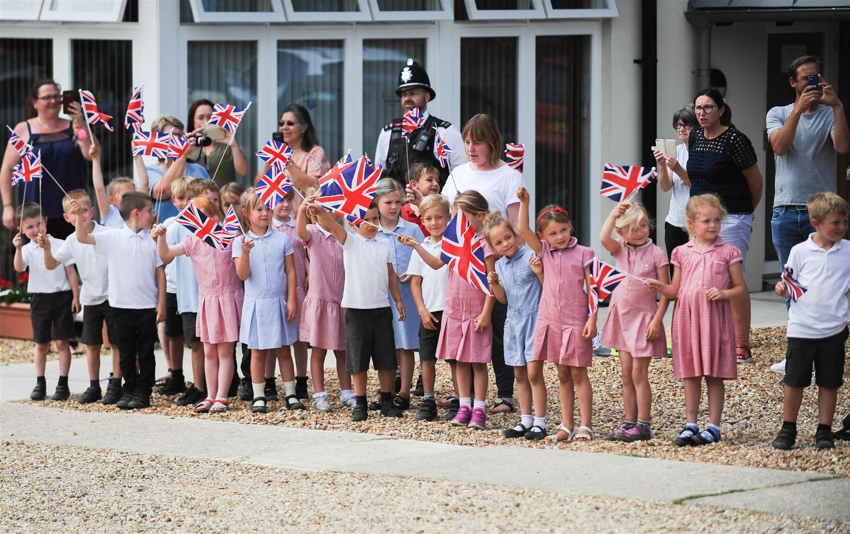 Pupils from Dersingham Primary School waved Union flags as HM The Queen arrived at the Dersingham Village Centre.. (13449429)