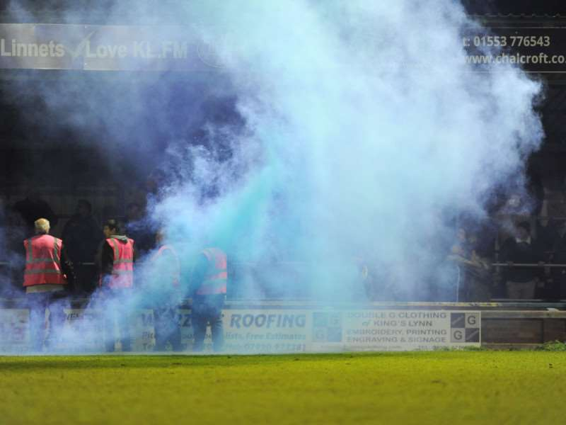 Smoke rises from the Walks pitch after the flare was thrown during Lynn's win over Hereford