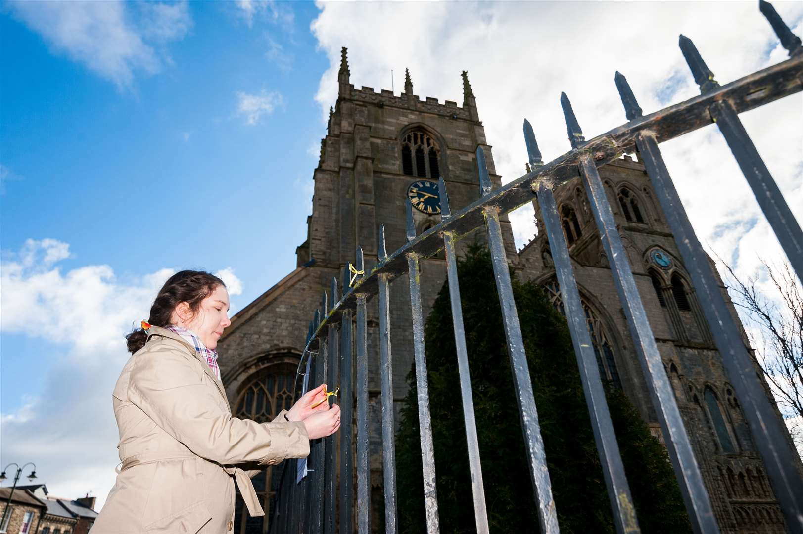 Engagement and development worker, Monika Saganowska, tying a yellow ribbon outside the King's Lynn Minster. Picture: ian Burt. (45391794)