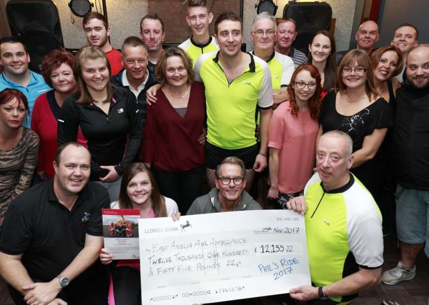 Presenting the cheque is Spike Dewing (front right) to Christopher Donaldson (front centre) of the East Anglia Air Ambulance with cyclist Katie Taggart (centre front left) and event organiser David Fletcher (front left), surrounded by just some of the many participants who took part on 2 wheels on 27th August. Photo: SUBMITTED.