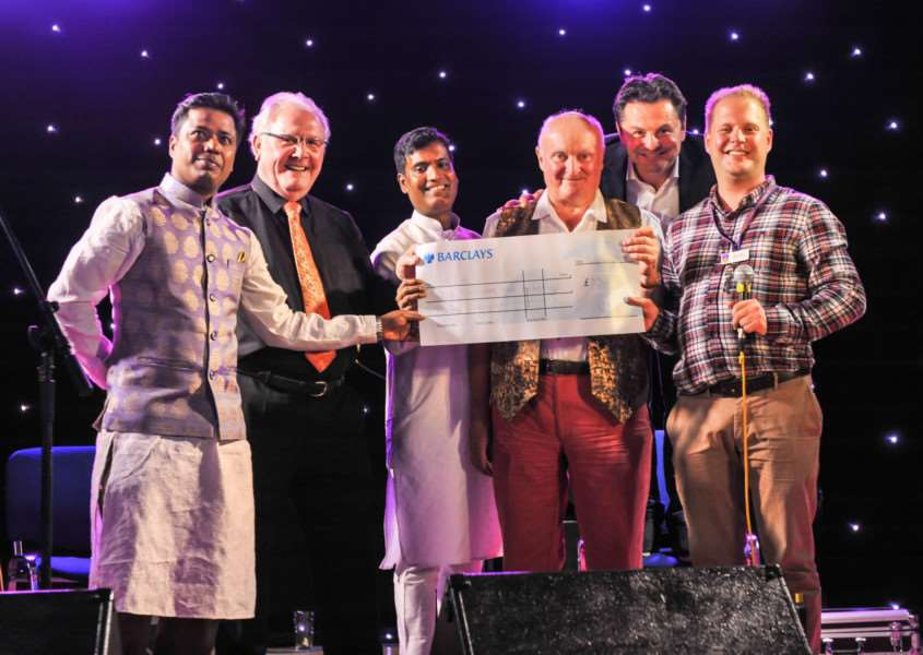 Staff at Downham Tandoori presenting a cheque of �3,500 to representatives from EACH, with BBC presenter Chris Hollins, who hosted the night, second from right. Photo: Chris Biele, PixBeat Photo.