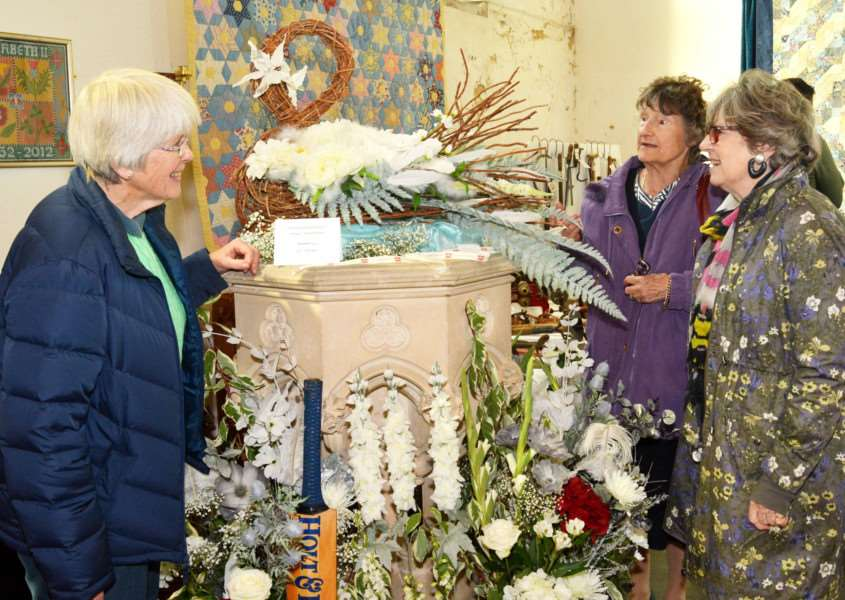 Flitcham Church Flower Festival'Church warden, Linda Neave (left), shows visitors, Iona Biggs and Roberta Wood, a flower arrangement with cricket bat and a swan shaped basket representing former international cricketer Graeme Swann