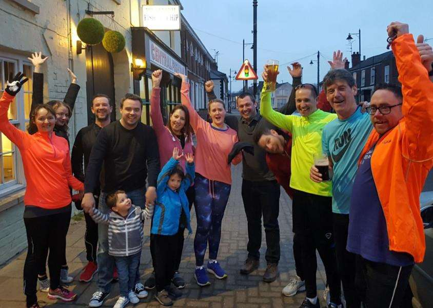 Nick Franklin (third right) is welcomed back by friends outside The Horse and Groom, Holbeach, after finishing five half Ironmans in five days to raise money for the British Heart Foundation, Cancer Research UK and West Norfolk Mind. Photo supplied.