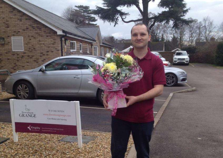 Downham Grange Support worker Andrei Nemetti receiving the flowers from West Norfolk Flowers of Wimbotsham. Photo: SUBMITTED.