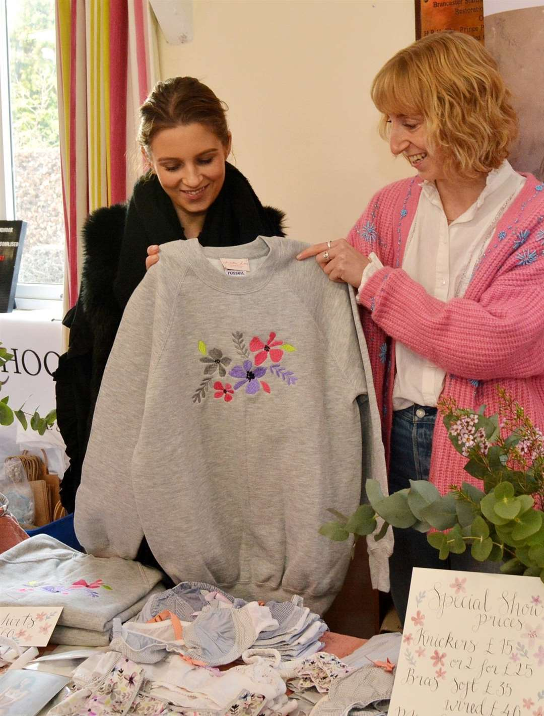 Mimi Emmett checks out one of Martha Coomber's sweaters for size on her Lounge Wear stall (6066412)