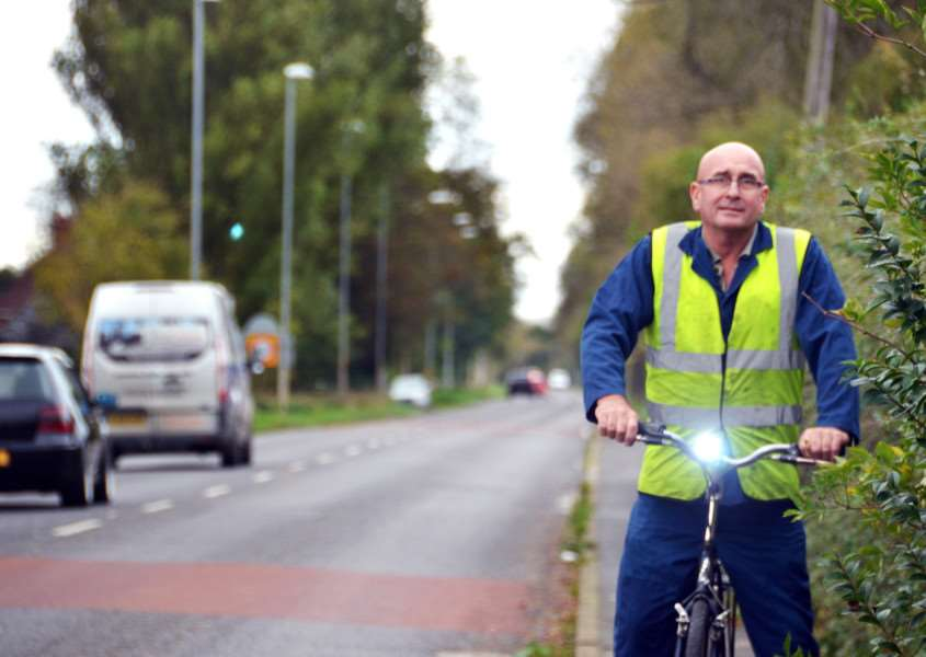 Sutton Bridge, John Jackson biking on section of road where lights are switched-off. John breaks rules and cycles on paths despite overgrown hedges due close shaves with traffic.