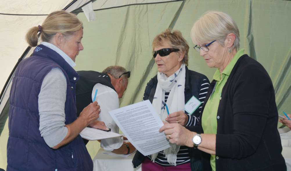 Astro Brain Tumour Walk at Holkham Hall'Two walkers sign in helped by volunteers Pat Dawson and treasurer Mary Burton