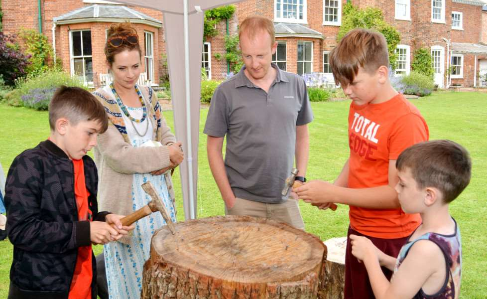 WEST ACRE VILLAGE FETE'Stall holders Fiona Elsey and John Harrison watch, from left, Jack Elsey, Ty Zochowski and Ben Elsey compete to see who can hammer a nail into a tree trunk quickest
