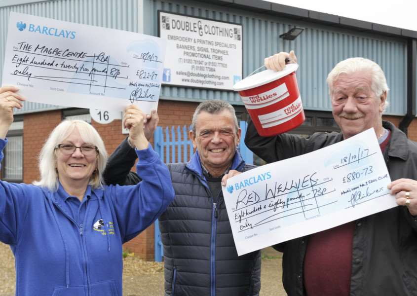 Two cheques presented at Double G Clothing King's Lynn'Gordon Chilvers (Centre) (from Double G Clothing), presenting cheques to Jan Calvert (left) (Tres WNRDA The Magpie Centre) and Mervyn Wiles (right) (Red Wellies)