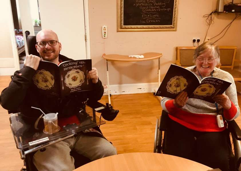 Adam Pearson and Hazel Dixon from Meadow House with their copy of Cooking Up Memories