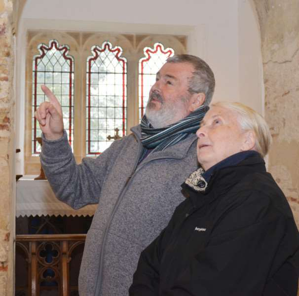 St Mary's, Houghton on the Hill'Trustee Alan Brinsdon explains one of the murals to visitor Lesley Parsonson