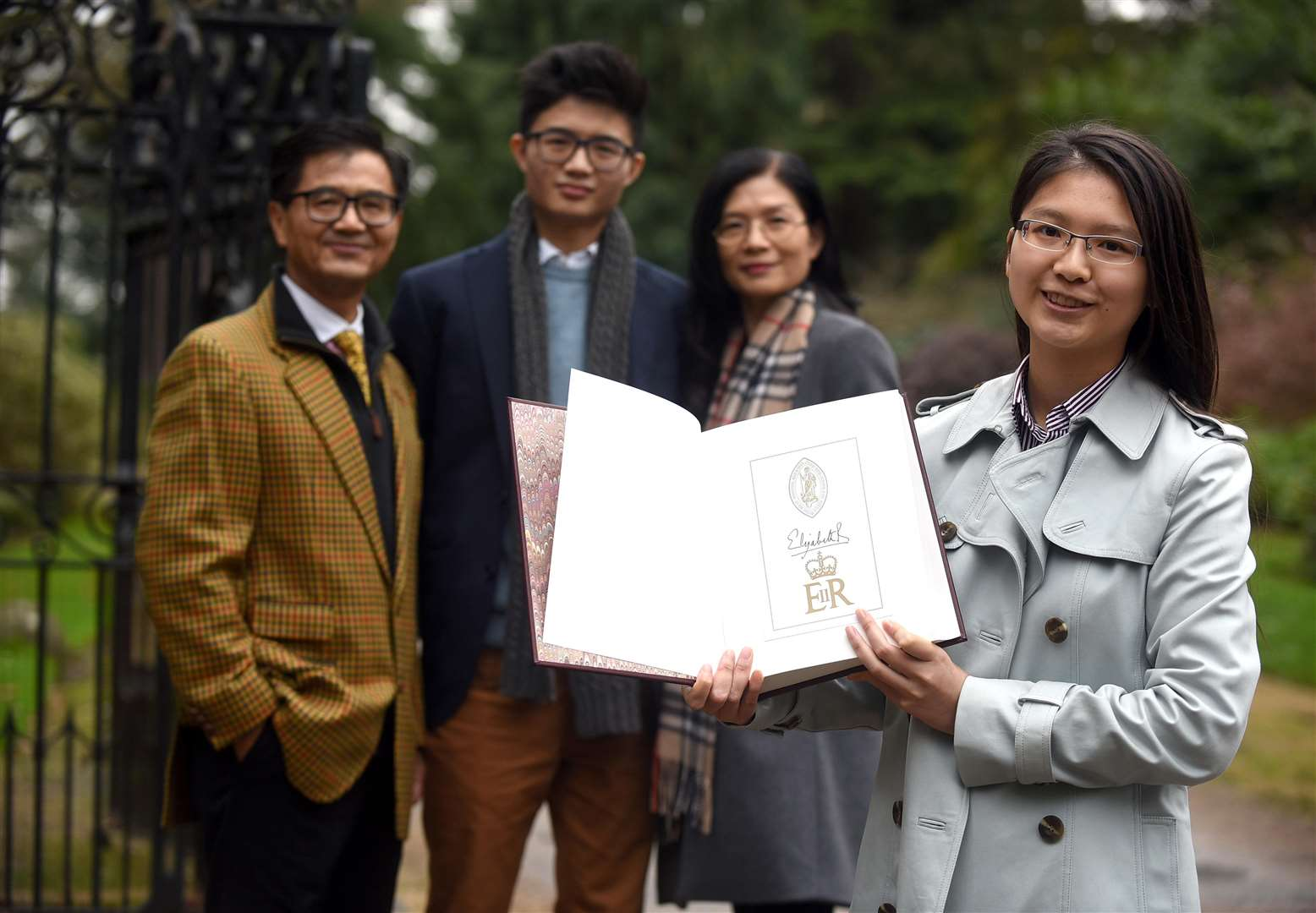 Florence Chung with The Complete Works of Shakespeare book been signed by The Queen..back left to right Jeff Chung, Clement Chung and Sierra Chung. (6475166)