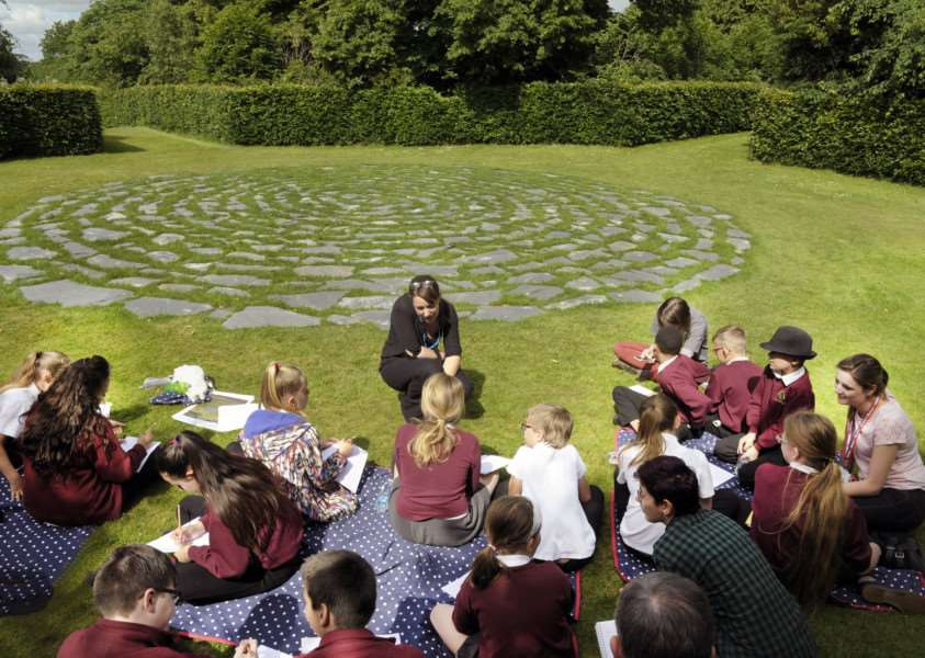 BeLong Education Project at Houghton Hall with pupils from Fairstead Primary School, King's Lynn 'Writer Annetta Berry with some of the pupils at the Wilderness Dreaming Cornish Slate Sculpture