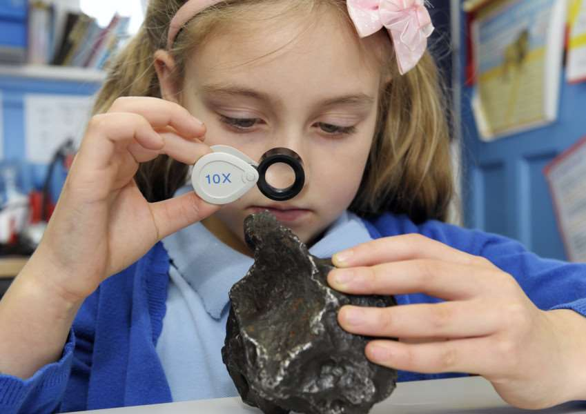 Science Federation Day at Sedgeford Primary School with Children from Sedgeford, Brancaster and Docking Schools''Sedgeford pupil Katie Chell-Williams taking a close up look at the Large Campo de Cielo Iron Meteorite