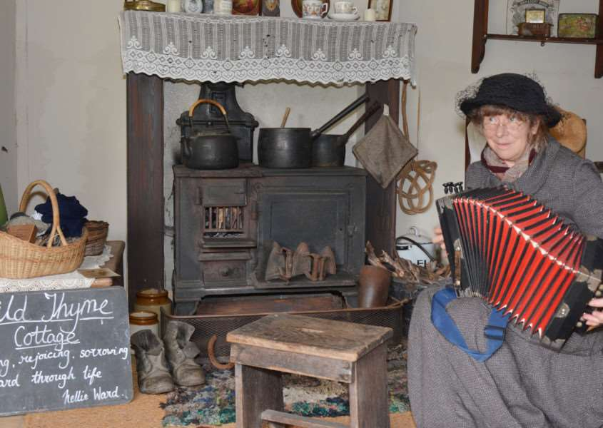 150 YEARS OF ROUGHAM LIFE'Sally North, in period dress, plays a melodeon in a recreation of a Victorian kitchen