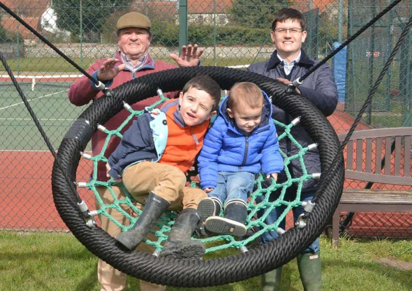 Three generations enjoy the new Burnham Market play area - grandfather Russell Cooper (back, left) and son Matthew help youngsters William and George get into the swing